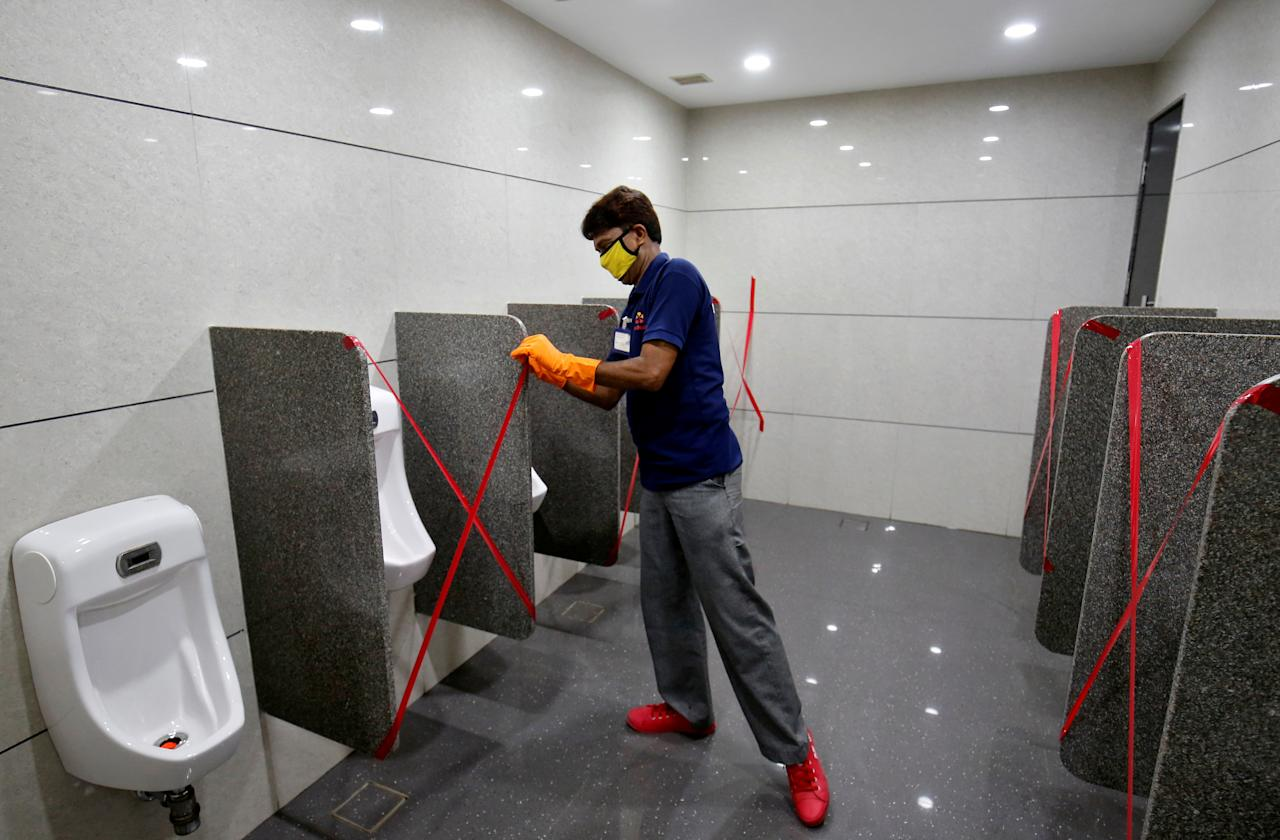 A worker applies tape markings on urinals to encourage social distancing at a shopping mall after authorities allowed malls to reopen as India eases lockdown restrictions that were imposed to slow the spread of the coronavirus disease (COVID-19), in Ahmedabad, India, June 8, 2020. REUTERS/Amit Dave