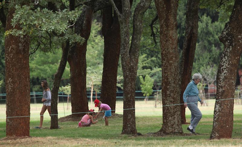 """in this photo taken Monday, June 3, 2013, a family plays underneath the indigenous msasa trees at the Royal Harare Golf Club. Club manager Ian Mathieson says a program to cut down """"alien'' trees and replace them with trees """"indigenous"""" to Zimbabwe is well under way. (AP Photo/Tsvangirayi Mukwazhi)"""