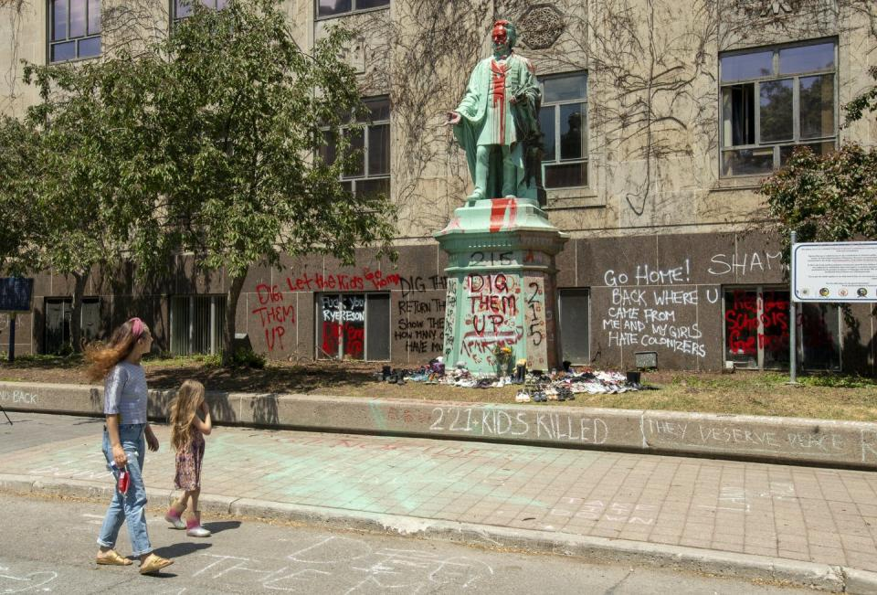 """<span class=""""caption"""">Shoes are placed at the base of the vandalized Egerton Ryerson statue at Ryerson University in Toronto. </span> <span class=""""attribution""""><span class=""""source"""">THE CANADIAN PRESS/Frank Gunn </span></span>"""