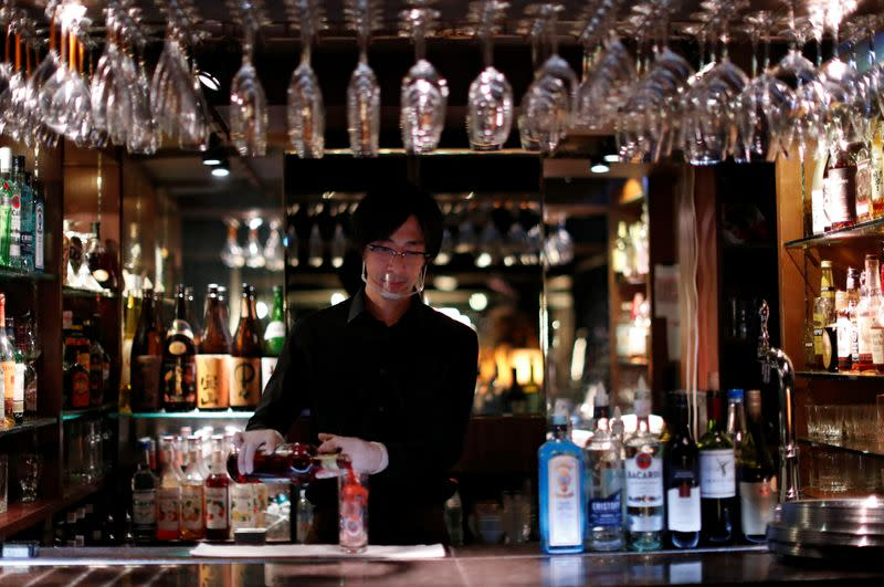 A bartender wearing a face shield makes a cocktail, amid the coronavirus disease (COVID-19) outbreak, at a night club in Tokyo