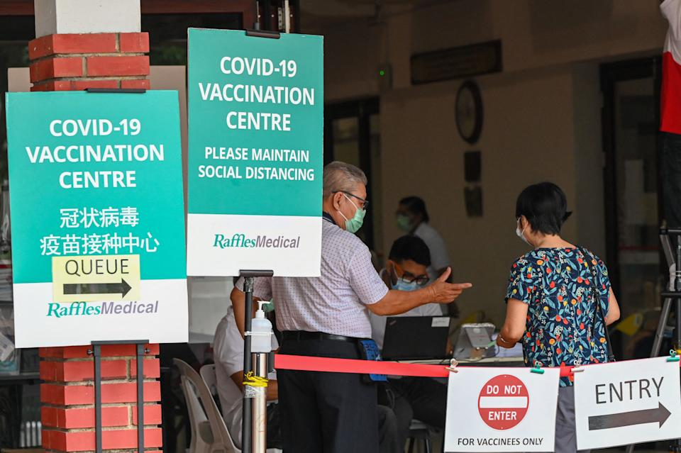 People enter a Covid-19 coronavirus vaccination centre set up at a community centre in Singapore on October 7, 2021. / AFP / Roslan Rahman