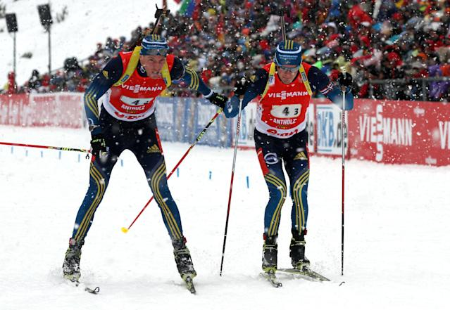 Sweden's Bjoern Ferry, left, passes to teammate Fredrik Lindstroem during a men's Biathlon 4x7,5 kilometer relay race in Anterselva, Italy, Sunday, Jan. 19, 2014. (AP Photo/Felice Calabro')