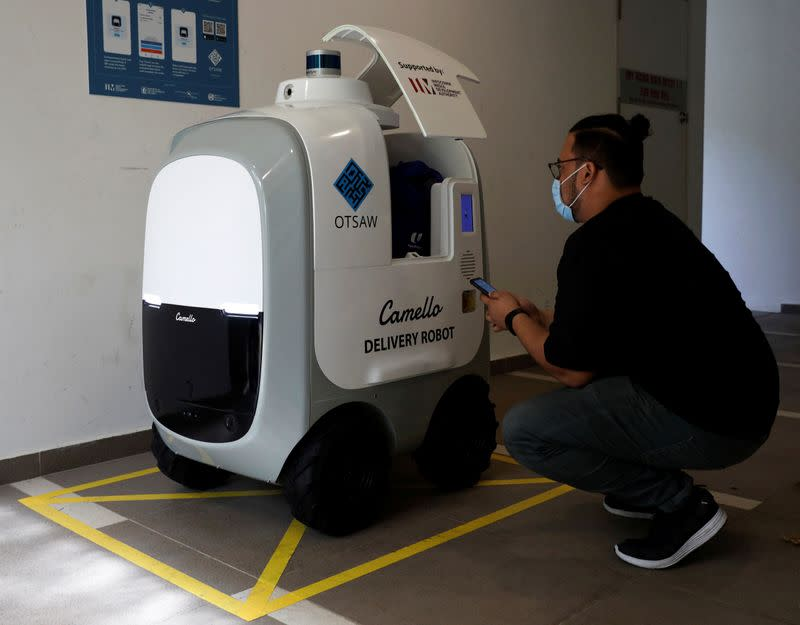 A customer collects his groceries from Carmello, an autonomous grocery delivery robot, in Singapore
