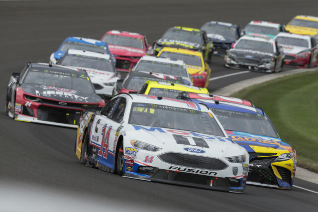 NASCAR Cup Series driver Clint Bowyer (14) leads a pack of cars through the first turn during the NASCAR Brickyard 400 auto race at Indianapolis Motor Speedway, in Indianapolis Monday, Sept. 10, 2018. (AP Photo/AJ Mast)
