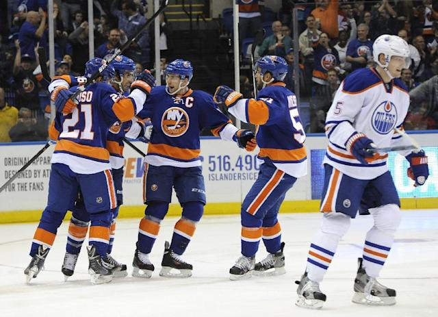 New York Islanders' Kyle Okposo (21), Matt Moulson (26), John Tavares (91) and Frans Nielsen (51) celebrates Okposo's goal as Edmonton Oilers' Ladislav Smid (5) skates away in the second period of an NHL hockey game on Thursday, Oct. 17, 2013, in Uniondale, N.Y. (AP Photo/Kathy Kmonicek)