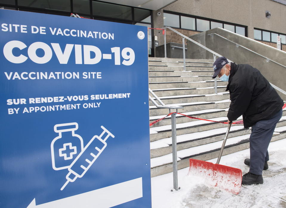 FILE - In this March 14, 2021, file photo, Yvan Courchesne clears snow from the steps of a COVID-19 vaccination site in Montreal as the pandemic continues in Canada and around the world. Canada once was hailed as a success story in dealing with the coronavirus pandemic, faring much better than the United States in deaths and infections because of how it approached lockdowns. But the trade-dependent nation has lagged on vaccinating its population because it has had to rely on the global supply chain. (Graham Hughes/The Canadian Press via AP, File)