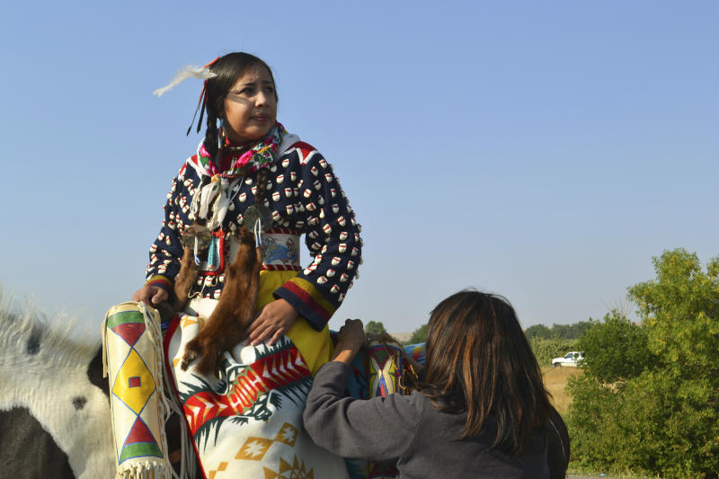 In this Friday, Aug. 18, 2017 photo, Julia Brien, left, prepares for the Crow Fair parade in Crow Agency, Mont. For the Crow Tribe, the eclipse coincides with the Parade Dance at the annual Crow Fair, marking the tribe's new year. (AP Photo/Mary Hudetz)