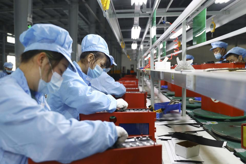 Employees working in the workshop of a lithium battery manufacturing company in Huaibei, eastern China's Anhui province