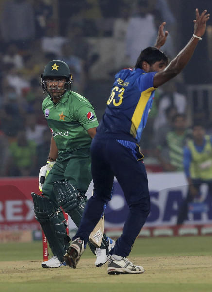 Pakistani batsman Umar Akmal, left, looks to umpire while Sri Lankan pacer Nuwan Pradeep appeals for his dismissal during first Twenty20 match at Gaddafi stadium in Lahore, Pakistan, Saturday, Oct. 5, 2019. (AP Photo/K.M. Chaudary)