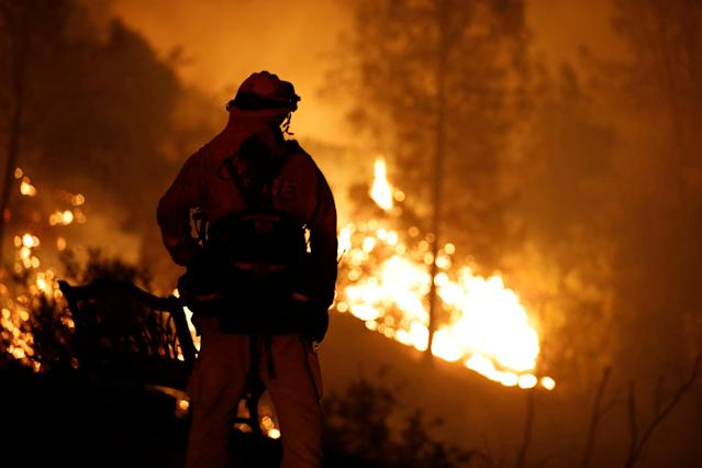 <p>A firefighter watches flames advance up a hill towards homes as crews battle the Carr Fire, west of Redding, Calif., July 27, 2018. (Photo: Fred Greaves/Reuters) </p>