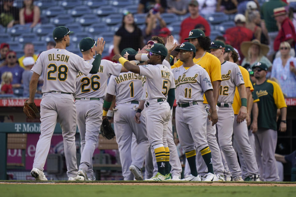 Oakland Athletics players celebrate a win over the Los Angeles Angels in a baseball game Sunday, Sept. 19, 2021, in Anaheim, Calif. (AP Photo/Jae C. Hong)