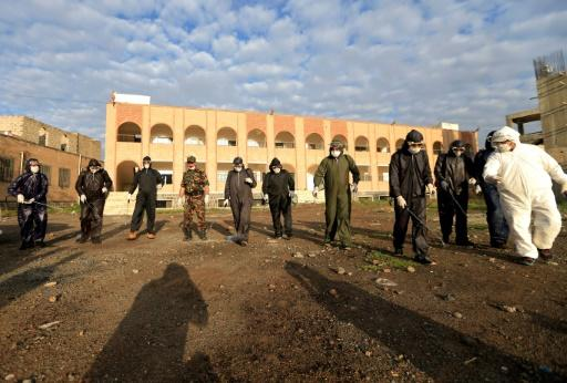 Personnel with Yemen's Central Security Forces, wearing full personal protective equipment,  disinfect an area outside a government building in Sanaa