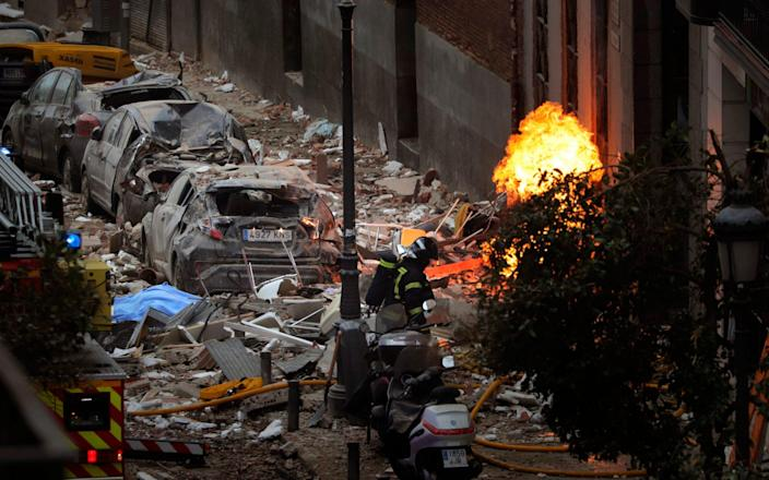 Wreckage lines the Madrid street as firefighters deal with explosion's aftermath - AP