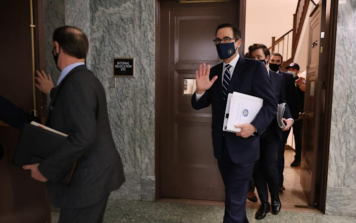 Wearing a face mask to reduce the risk of coronavirus, Treasury Secretary Steven Mnuchin (C) arrives at the weekly Senate Republican policy luncheon August 04, 2020 in Washington, DC. - Chip Somodevilla/Getty Images North America