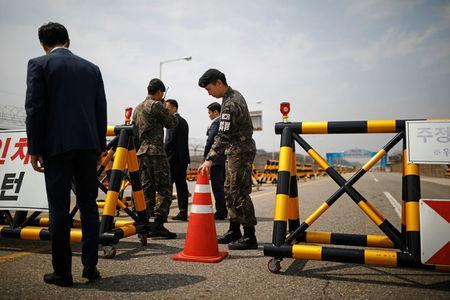 South Korean soldiers and security personnel stand guard at a checkpoint on the Grand Unification Bridge that leads to the Peace House, the venue for the Inter-Korean summit, near the demilitarized zone separating the two Koreas, in Paju, South Korea, April 26, 2018. REUTERS/Kim Hong-Ji