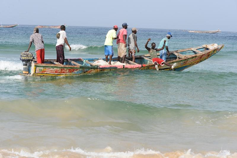 Senegalese fishermen ride a dugout canoe from Kayar beach out to sea, where they are facing competition from Chinese boats fishing illegally off the coast of West Africa, Greenpeace says (AFP Photo/Seyllou Diallo)