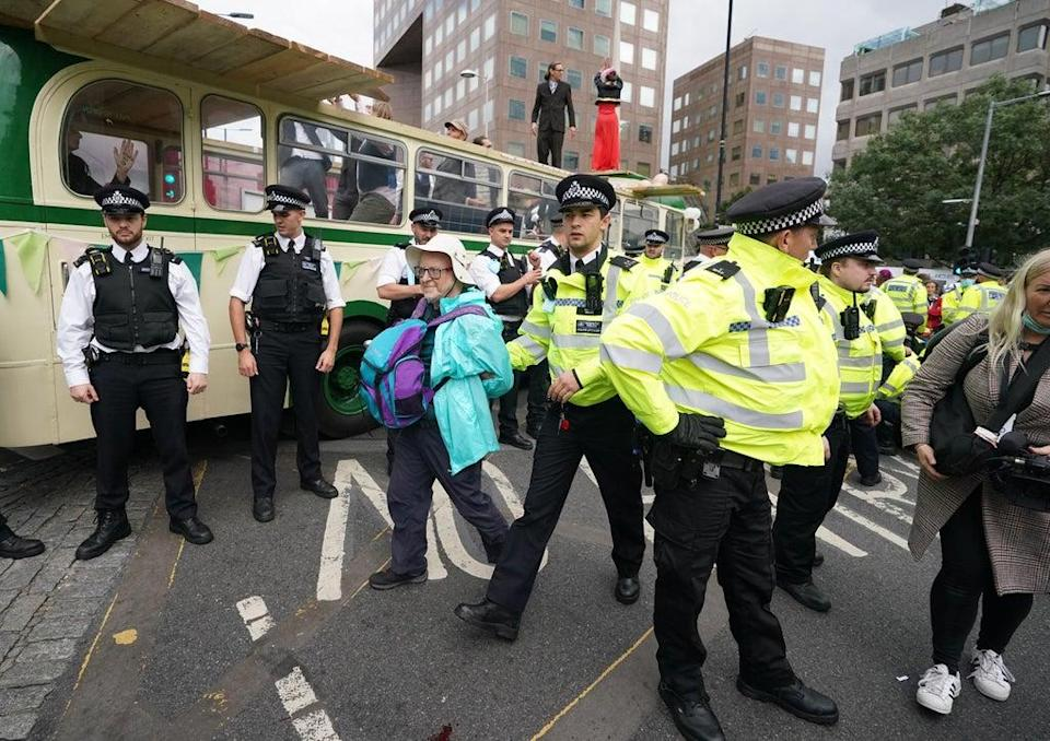 Police and demonstrators with a bus (Ian West/PA) (PA Wire)