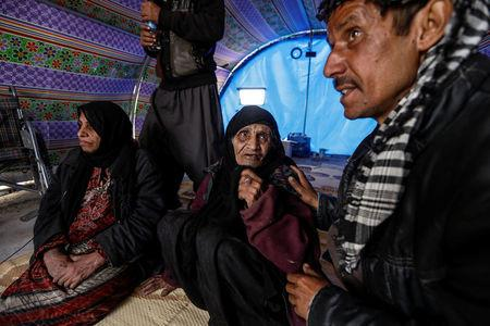 Khatla Ali Abdullah, 90, who recently fled her home in Al Mamoun district talks to her relative as she sits with her daughter (L) in her tent in Hammam al Alil camp, while Iraqi forces battle with Islamic State militants, in western Mosul, Iraq March 1, 2017.  REUTERS/Zohra Bensemra