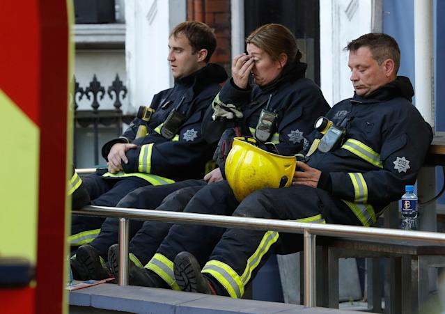 <p>Firefighters wait to start their shift after a massive fire raged in a 27-floor high-rise apartment building in London, Wednesday, June 14, 2017.(Matt Dunham/AP) </p>