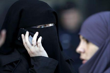 A women , wearing a niqab despite a nationwide ban on the Islamic face veil, gives a phone call outside the courts in Meaux