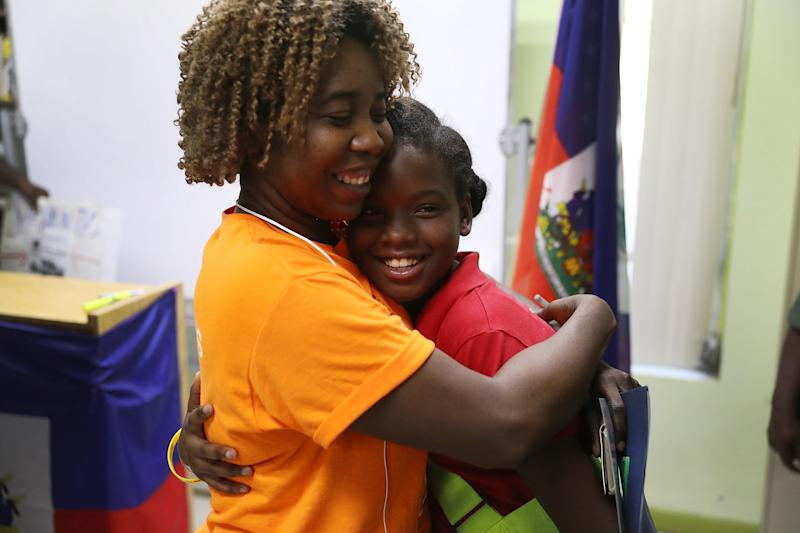 Santcha Etienne, left, hugs Ronyde Christina Ponthieux, 10, after she spoke at a newsconference at the office of the Haitian Women of Miami on Nov. 6. (Joe Raedle via Getty Images)