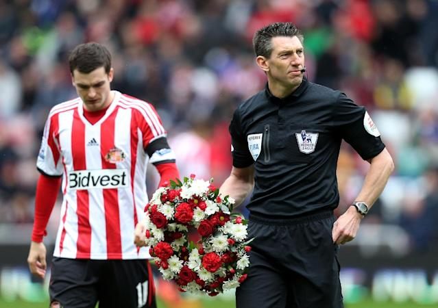 Referee Lee Probert, right, holds a wreath after the Sunderland and Everton players paid their respects ahead of their English Premier League soccer match at the Stadium of Light, Sunderland, England, Saturday, April 12, 2014. As a mark of respect and remembrance for those who lost their lives as a result of the Hillsborough tragedy in April 1989, all Premier League, Football League, Football Conference and FA Cup matches taking place this weekend will kick off seven minutes later than originally scheduled. (AP Photo/Scott Heppell)