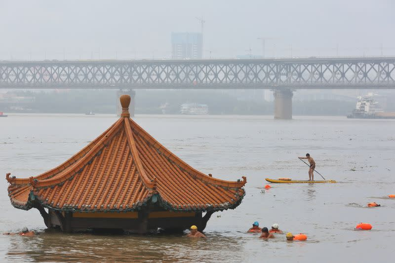 People swim near a pavilion partially submerged in floodwaters following heavy rainfall in Wuhan