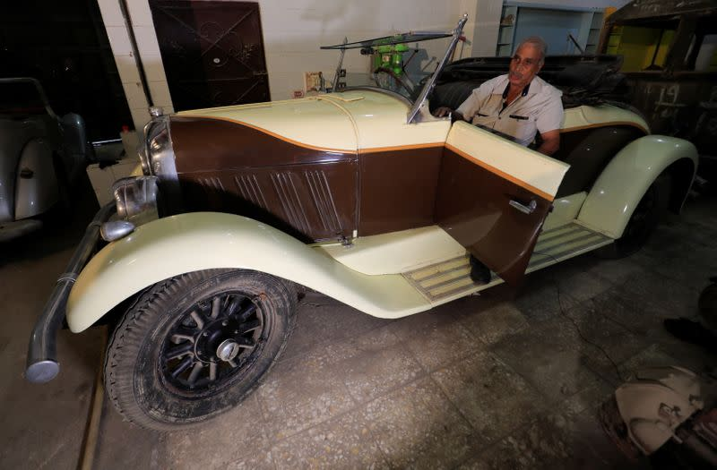 """Sayed Sima, a 70-years-old Egyptian collector of vintage cars, speaks during an interview with Reuters seated on a 120-year-old American """"1900 Auburn"""" automobile in his store in the Giza suburb of Abu Rawash"""