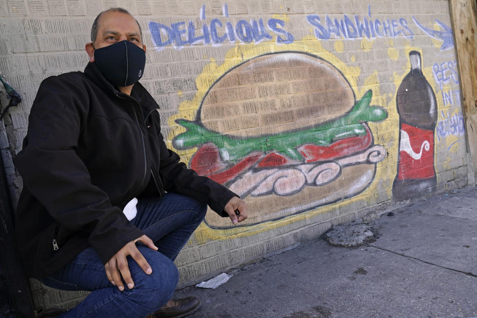 Bodega owner Francisco Marte poses in front of a sign outside his deli-style store, Wednesday, Feb. 10, 2021, in the Bronx borough of New York. Marte president of the Bodega and Small Business Association of New York, which represents bodegas in New York, says he's lobbied local officials to set aside COVID-19 vaccine appointments for bodega workers, many of whom are unaware they are eligible.(AP Photo/Kathy Willens)
