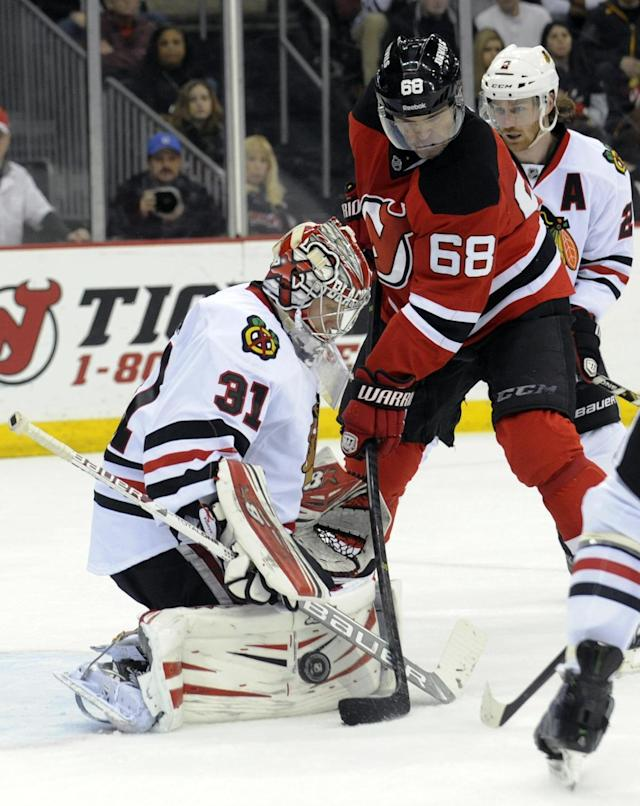 Chicago Blackhawks goaltender Antti Raanta, left, deflects the puck as New Jersey Devils' Jaraomit Jagr, of the Czech Republic, takes a shot during the second period of an NHL hockey game, Friday, Jan. 3, 2014, in Newark, N.J. (AP Photo/Bill Kostroun)