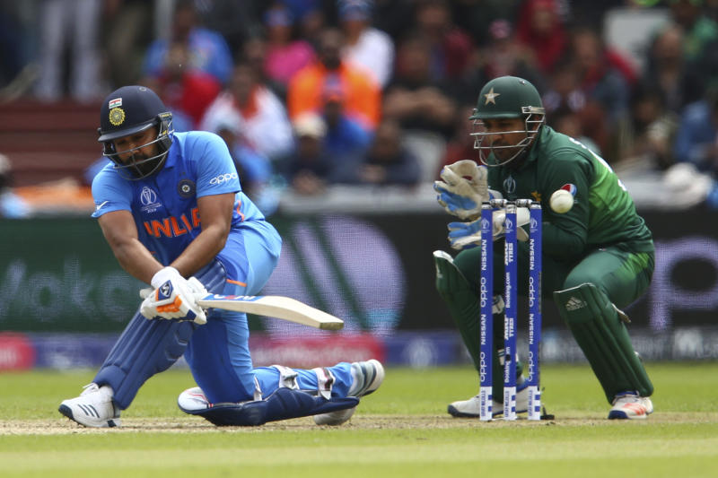 India's Rohit Sharma plays a shot under the watch of Pakistan's captain Sarfaraz Ahmed during the Cricket World Cup match between India and Pakistan at Old Trafford in Manchester, England, Sunday, June 16, 2019. (AP Photo/Dave Thompson)
