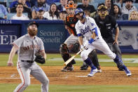 Los Angeles Dodgers' Chris Taylor, second from right, heads to first on a two-run home run while San Francisco Giants relief pitcher John Brebbia, left, watches long with catcher Buster Posey, second from left, and home plate umpire Dan Iassogna during the sixth inning of a baseball game Tuesday, July 20, 2021, in Los Angeles. (AP Photo/Mark J. Terrill)