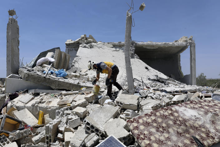 A civil defense worker inspects a damage house after shelling hit the town of Ibleen, a village in southern Idlib province, Syria, Saturday, July 3, 2021. Artillery fire from government-controlled territory Saturday killed at least eight civilians in Syria's last rebel enclave, most of them children, rescue workers and a war monitor said. (AP Photo/Ghaith Alsayed)
