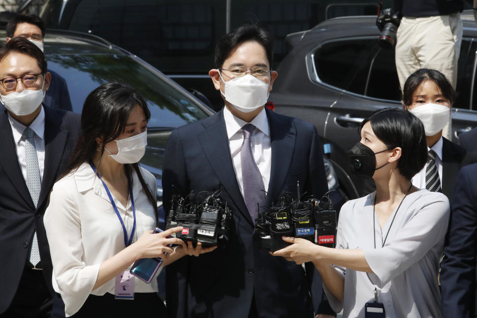 FILE - In this June. 8, 2020, file photo, Samsung Electronics Vice Chairman Lee Jae-yong, center, arrives at the Seoul Central District Court in Seoul, South Korea. Pressure is mounting on South Korean President Moon Jae-in to pardon Samsung heir Lee Jae-yong, who is back in prison after his conviction in a massive corruption scandal, even though business has rarely looked better at South Korea's largest company. (AP Photo/Ahn Young-joon, File)