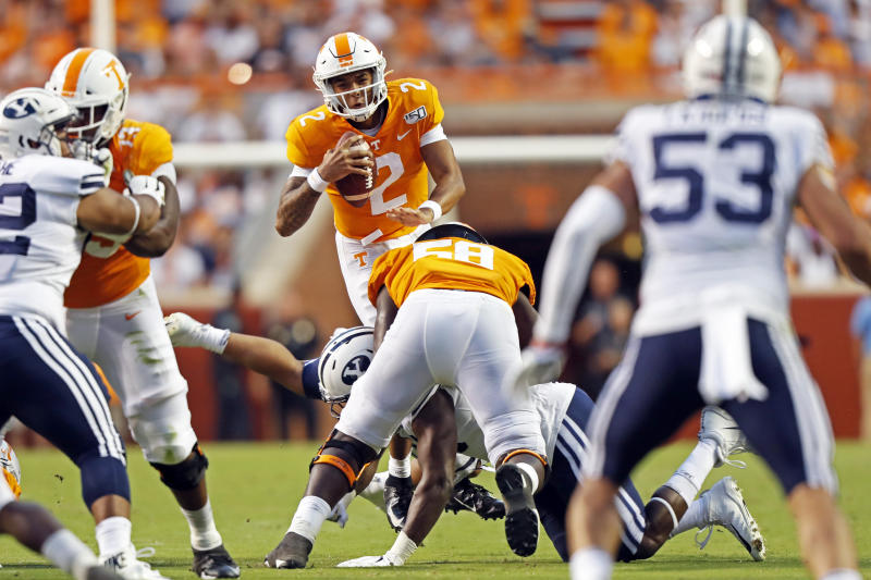 Tennessee quarterback Jarrett Guarantano (2) leaps over a Brigham Young defender in the first half of an NCAA college football game Saturday, Sept. 7, 2019, in Knoxville, Tenn. (AP Photo/Wade Payne)