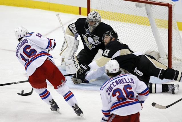New York Rangers' Derick Brassard (16) puts the puck past Pittsburgh Penguins goalie Marc-Andre Fleury (29) and Robert Bortuzzo (41) for the game-winning goal in the first overtime period of Game 1 of a second-round NHL hockey playoff series in Pittsburgh, Friday, May 2, 2014. The Rangers won 3-2. (AP Photo/Gene J. Puskar)