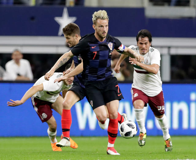 In this Photo taken on Tuesday, March 27, 2018, Croatia midfielder Ivan Rakitic, foreground, leads an attack as Mexico midfielder Jorge Hernandez, right, gives chase during the first half of an international friendly soccer match in Arlington, Texas. (AP Photo/Tony Gutierrez)