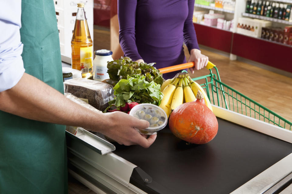 A cashier at a grocery store rings in items at a till. (Getty)