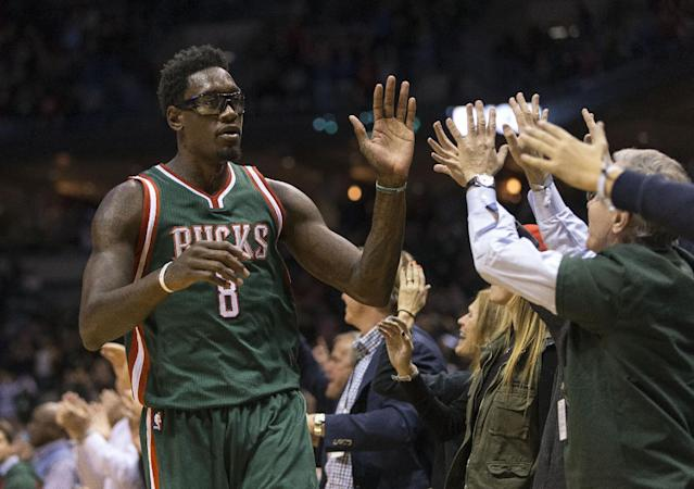 Milwaukee Bucks' Larry Sanders (8) high-fives fans after his team defeated the Philadelphia 76ers in an NBA basketball game Friday, Oct. 31, 2014, in Milwaukee. (AP Photo/Tom Lynn)
