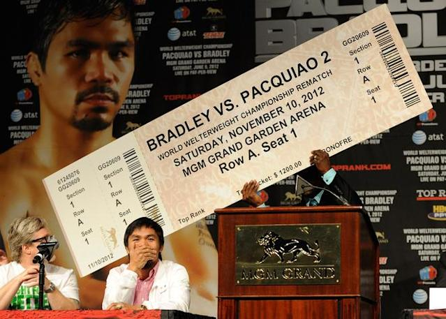 LAS VEGAS, NV - JUNE 06: Boxer Timothy Bradley (R) holds up an oversize fake ticket predicting a rematch with trainer Freddie Roach (L) and boxer Manny Pacquiao during the final news conference for their bout at the MGM Grand Hotel/Casino June 6, 2012 in Las Vegas, Nevada. Pacquiao will defend his WBO welterweight title against Bradley when the two meet in the ring on June 9 in Las Vegas. (Photo by David Becker/Getty Images)