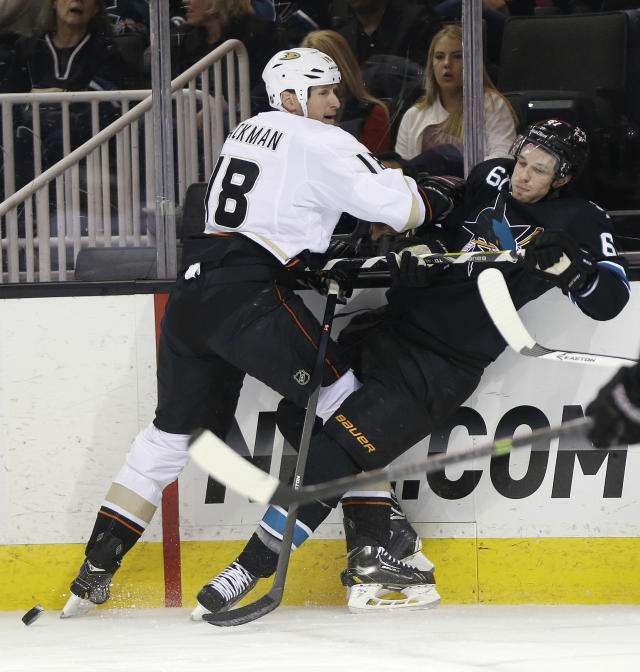 Anaheim Ducks' Tim Jackman, left, crashes against the boards next to San Jose Sharks' Justin Braun during the second period of an NHL hockey game Thursday, March 20, 2014, in San Jose, Calif. (AP Photo/Marcio Jose Sanchez)