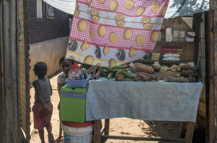 A woman sells vegetables in the slum district of Mont Baduel, in Cayenne, French Guiana, Friday, July 10, 2020. France's most worrisome virus hotspot is in fact on the border with Brazil - in French Guiana, a former colony where health care is scarce and poverty is rampant. The pandemic is exposing deep economic and racial inequality in French Guiana that residents say the mainland has long chosen to ignore. (AP Photo/Pierre Olivier Jay)