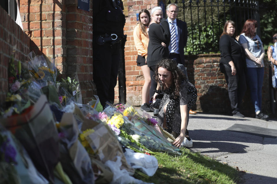 Flowers are placed at the entrance to the Holt School, in Wokingham, England, in memory of teacher James Furlong, a victim of a terror attack in nearby Reading, Monday June 22, 2020.  A lone terror suspect remains in custody accused of killing three people and wounding three others in a Reading park on Saturday night. (Steve Parsons/PA via AP)