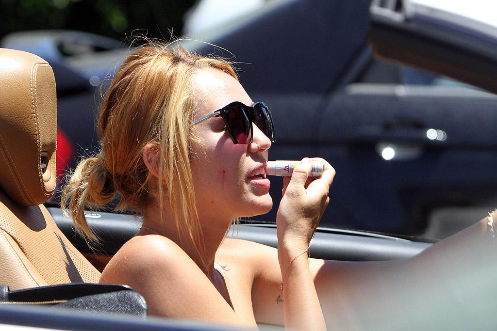 """After her fast-food run, Miley <span style=""""font-size:11.0pt; """">–</span> sporting bad skin and what looked like a hickey on her neck <span style=""""font-size:11.0pt; """">–</span> waited in the car (and applied lip gloss) while her pal ran into a liquor store. We can only assume that 19-year-old Miley stayed far away from the booze! (6/28/2012)"""