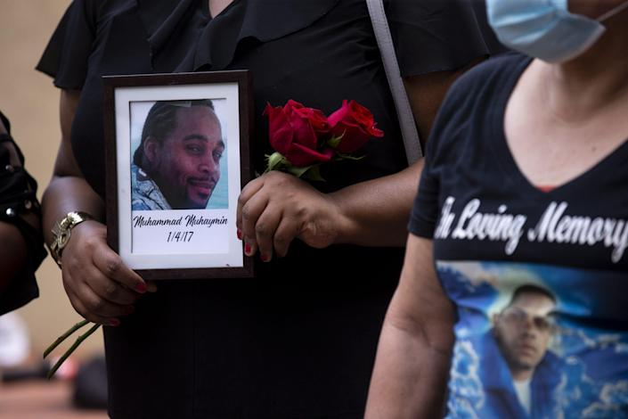 A family member of Muhammad Muhaymin holds a photo of him during a press conference regarding families who have had relatives killed by Phoenix police on Aug. 26, 2020, outside Phoenix City Council Chambers in Phoenix.