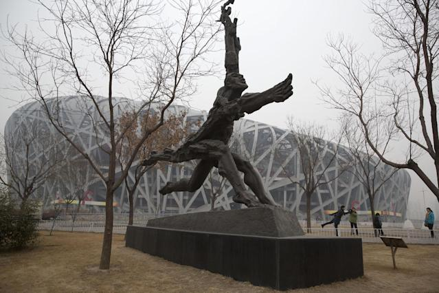 In this picture taken, Sunday, Feb. 23, 2014, a tourist poses near giant sculptures near the iconic Bird's Nest National Stadium in Beijing, China. The National Stadium, nicknamed the Bird's Nest because of its lattice design, has become a key Beijing landmark and a favored backdrop for visitors' snapshots. But few tourists are willing to pay more than $8 to tour the facility as enthusiasm for the 2008 Games fades, and the venue has struggled to fill its space with events. Beijing, which spent more than $2 billion to build 31 venues for the 2008 Summer Games, is reaping some income and tourism benefits from two flagship venues, though many sites need government subsidies to meet hefty operation and maintenance costs. (AP Photo/Ng Han Guan)