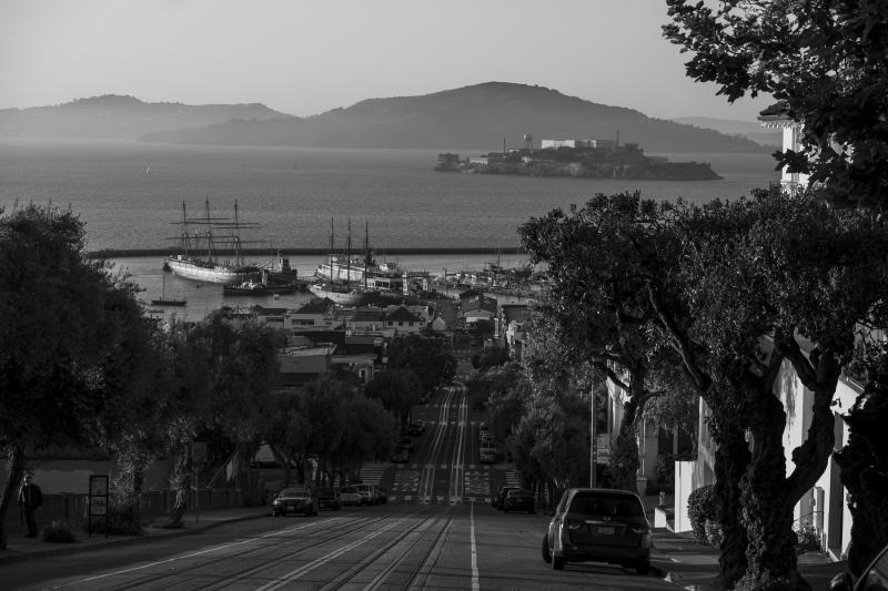 Cars are parked along an empty Hyde Street looking down toward the historic ships at Hyde Street pier and Alcatraz Island in San Francisco on May 7, 2020. Normally, the months leading into summer bring bustling crowds to the city's famous landmarks, but this year, because of the coronavirus threat they sit empty and quiet. Some parts are like eerie ghost towns or stark scenes from a science fiction movie. (AP Photo/Eric Risberg)