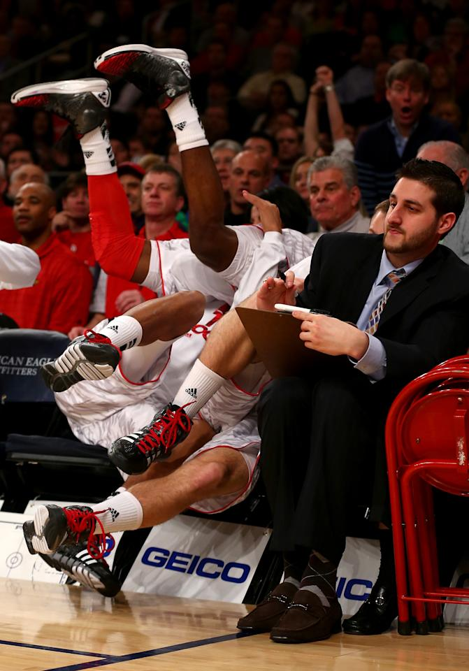 Russ Smith of the Louisville Cardinals falls over a teammate on the bench out of bounds in the first half against the Syracuse Orange during the final of the Big East Men's Basketball Tournament at Madison Square Garden on March 16, 2013 in New York City.  (Photo by Elsa/Getty Images)