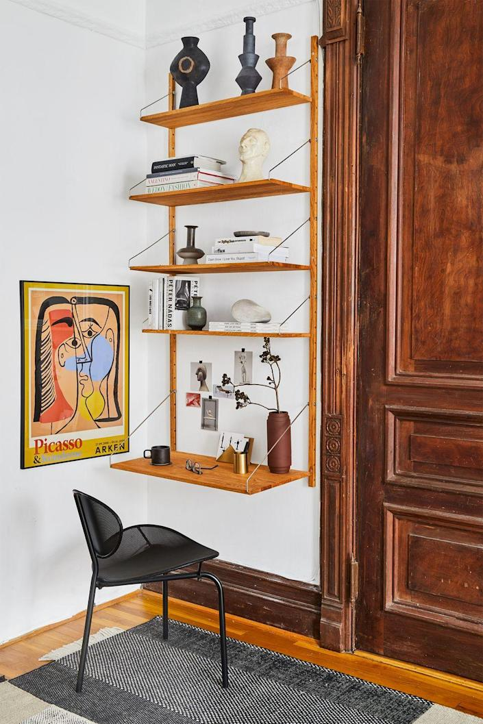 """<p>By installing a shelving unit on the wall in an unused corner of his apartment, <a href=""""https://www.instagram.com/tariqdixon/?hl=en"""" rel=""""nofollow noopener"""" target=""""_blank"""" data-ylk=""""slk:Tariq Dixon"""" class=""""link rapid-noclick-resp"""">Tariq Dixon</a>, co-founder of furniture brand TRNK, turned a tiny space into a writer's retreat. </p>"""