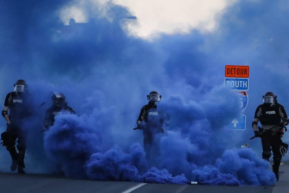 """FILE - In this May 30, 2020, file photo, police in riot gear walk through a cloud of blue smoke as they advance on protesters near the Minneapolis 5th Precinct in Minneapolis. Former Minneapolis police Officer Derek Chauvin faces decades in prison when he is sentenced Friday, June 25, 2021, following his murder and manslaughter convictions in the death of George Floyd. Floyd's death, filmed by a teenage bystander as Chauvin pinned Floyd to the pavement for about 9 and a half minutes and ignored Floyd's """"I can't breathe"""" cries until he eventually grew still, reignited a movement against racial injustice that swiftly spread around the world and continues to reverberate.(AP Photo/John Minchillo, File)"""